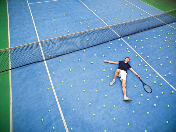 Male tennis player lying on ground stock photo