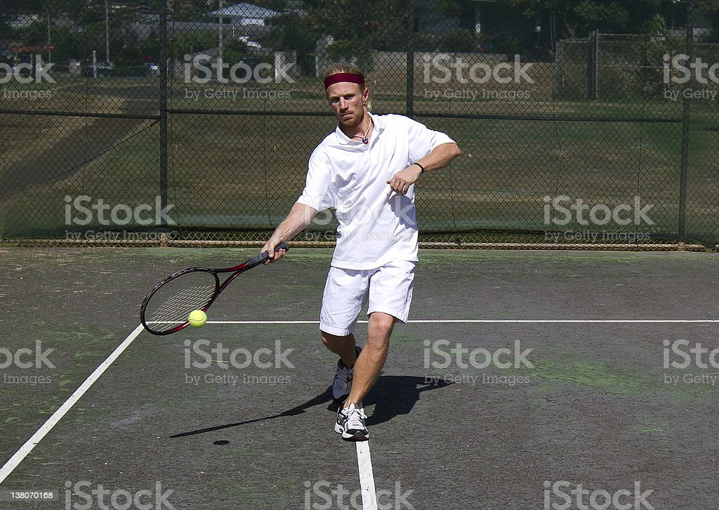 Male tennis player takes a swing stock photo