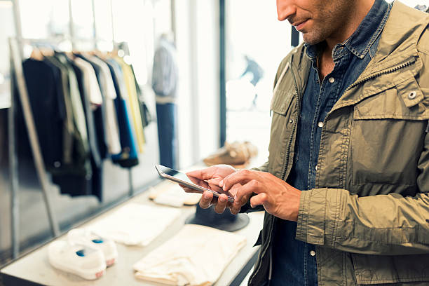 Male texting on smartphone in clothing store. Sms, message, mail stock photo