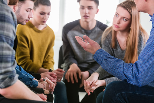 Male Therapist Assisting Depressed Young Student Stock Photo - Download Image Now