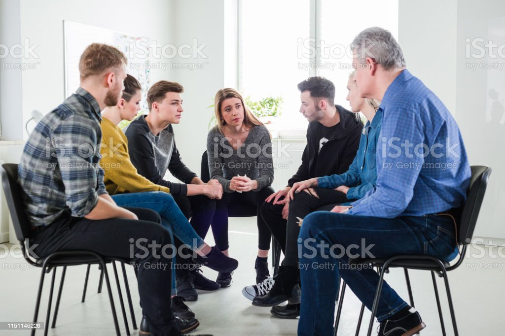 Male therapist assisting depressed young students Mature male therapist assisting depressed young students during meeting. Men and women are sitting with mental health professional. They are in lecture hall during group therapy. 18-19 Years Stock Photo