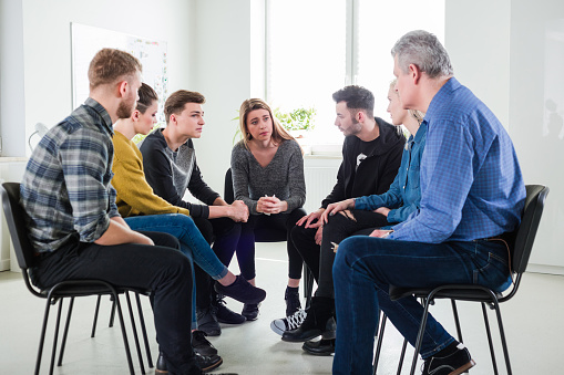 Male Therapist Assisting Depressed Young Students Stock Photo - Download Image Now