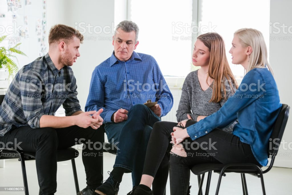 Male therapist discussing with young students Mental health therapist discussing with university students. Young man and women are sitting in university during group therapy. They are in lecture hall during meeting. 18-19 Years Stock Photo