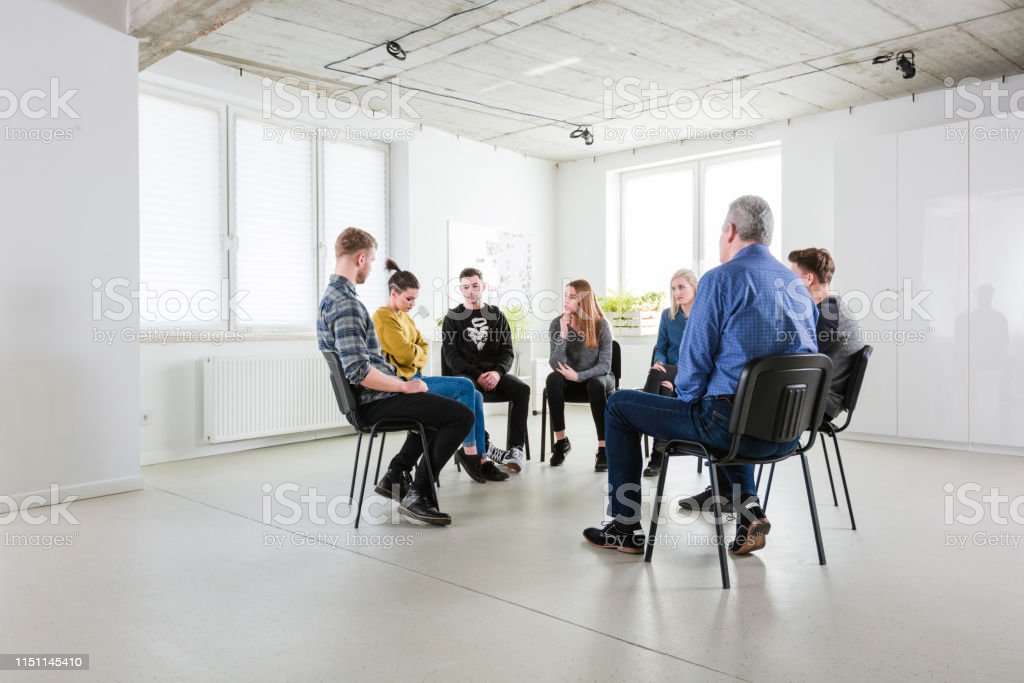 Male therapist discussing with young students Mental health therapist discussing with university students. Young men and women are sitting in university during group therapy. They are in lecture hall during meeting. 18-19 Years Stock Photo