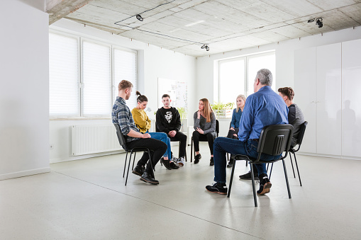 Male Therapist Discussing With Young Students Stock Photo - Download Image Now