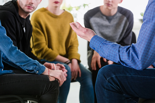 Male Therapist Gesturing To University Students Stock Photo - Download Image Now