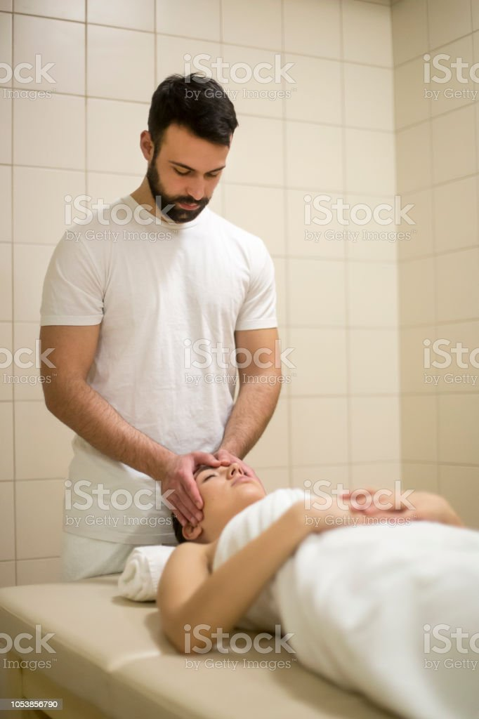 Young woman at a health spa having a head massage by a male...