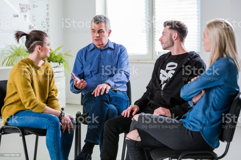 Male therapist giving advice to young students Mature mental health professional giving advice to young students at university. Man and women are listening solution from social worker. They are sitting in group therapy. 18-19 Years Stock Photo