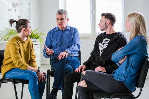 Male Therapist Giving Advice To Young Students Stock Photo - Download Image Now