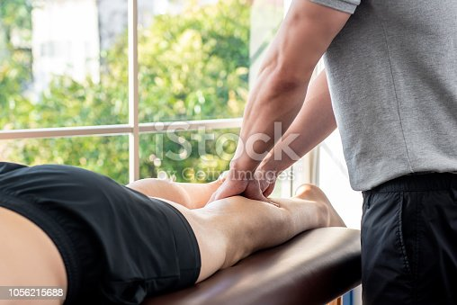 istock Male therapist giving leg massage to athlete patient in clinic 1056215688