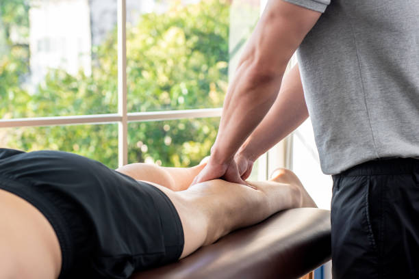 piernas dando terapeuta masculino masaje paciente atleta en clínica - masaje deportivo fotografías e imágenes de stock