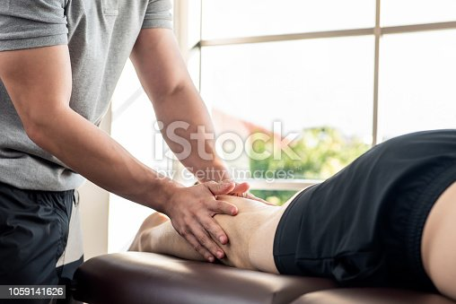 istock Male therapist giving leg massage to athlete patient on the bed in clinic 1059141626