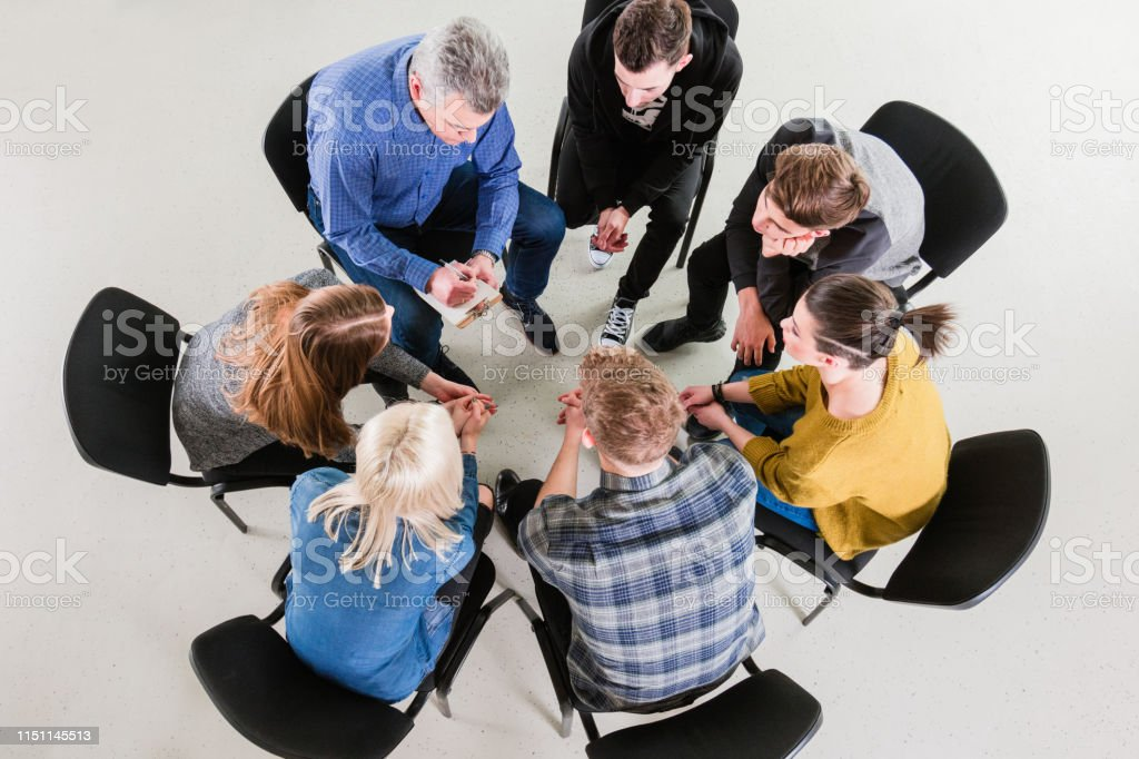 Male therapist giving solution to young students High angle view of mental health professional giving solution to university students. Therapist is sitting with young men and women during meeting. They are in group therapy at lecture hall. 18-19 Years Stock Photo