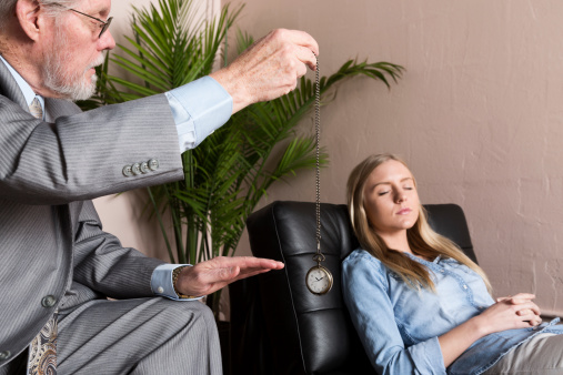 Male Therapist Using Hypnosis Therapy On Young Woman Stock Photo - Download Image Now