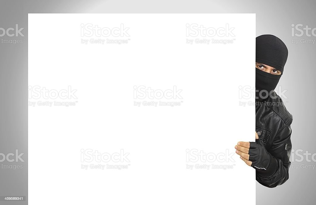 Male thief wearing black hiding behind white panel stock photo