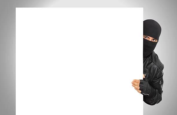 macho ladrón wearing black escudan detrás de panel blanco - ninja fotografías e imágenes de stock