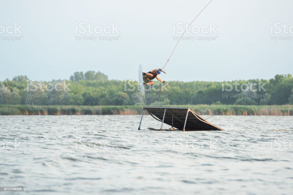Male thrill-seeker perfroming extreme midair stunts with wakeboard stock photo