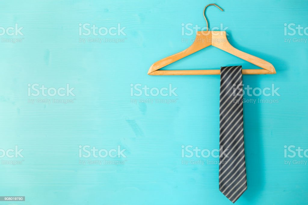 Male tie hanging on the rack, blue background. Father's day concept stock photo