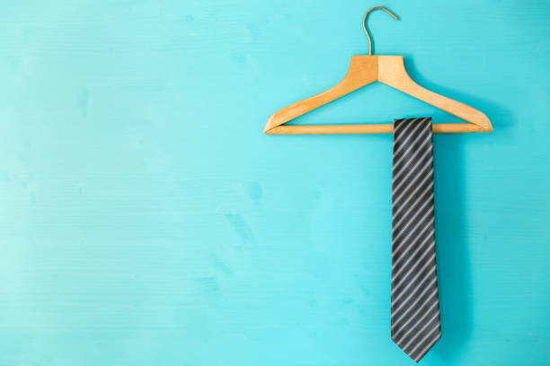 male tie hanging on the rack, blue background. father's day concept - галстук стоковые фото и изображения