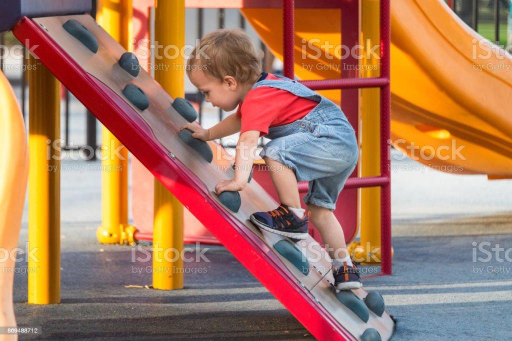 Masculino criança brincar no parque infantil - foto de acervo