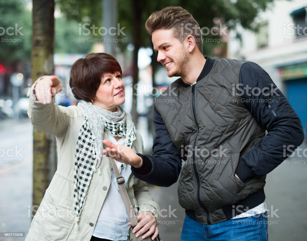 Male tourist asks for directions from woman - Foto stock royalty-free di Adulto