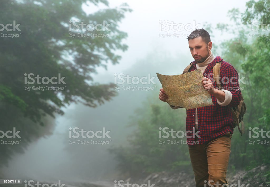Male tourist in woods in mountains with a map stock photo