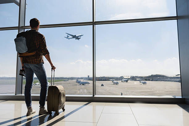 Male tourist looking at flight Young man is standing near window at the airport and watching plane before departure. He is standing and carrying luggage. Focus on his back passenger stock pictures, royalty-free photos & images