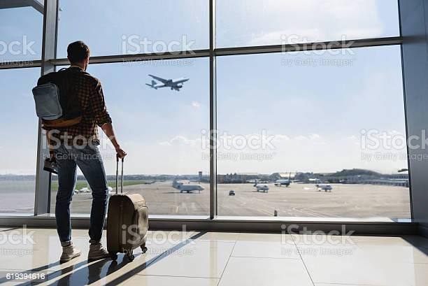 Männlicher Tourist Mit Blick Auf Den Flug Stockfoto und mehr Bilder von Flughafen