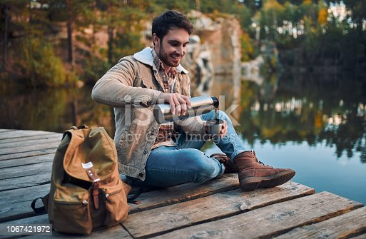 Male tourist exploring new places. Handsome bearded man on nature. Sitting with thermos and drinking tea near lake.