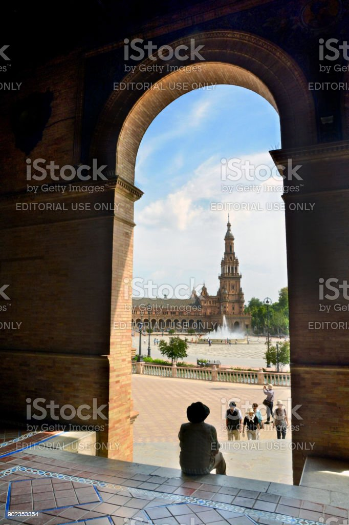 Male Tourist Sits Under a Peaceful Archway at the Seville Expo on a Hot Summer Day. stock photo