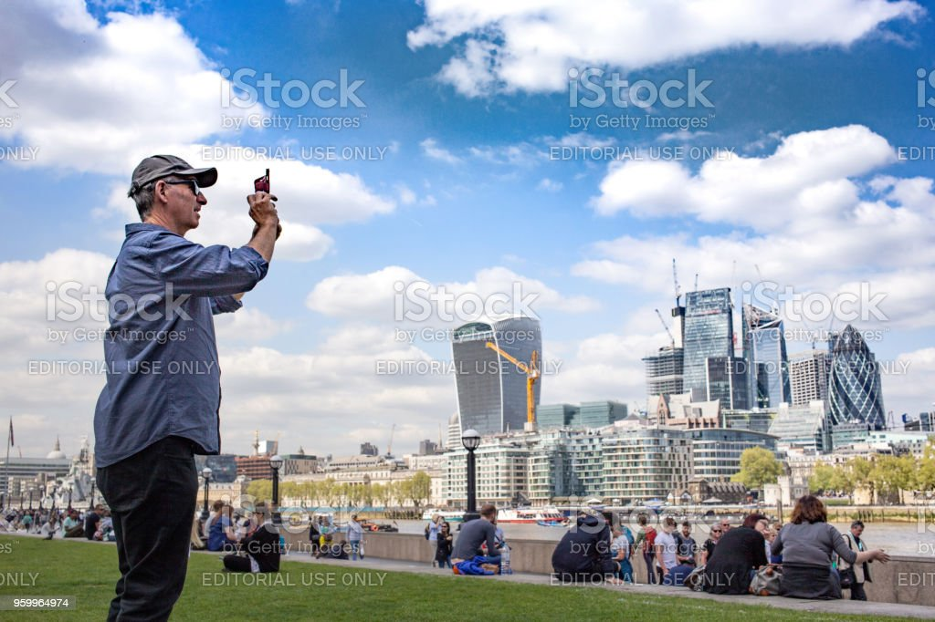 Male Tourist taking a picture of the London skyline around the London Riverside area near Potters Fields Park with the famous Walkie-Talkie building on the horizon stock photo