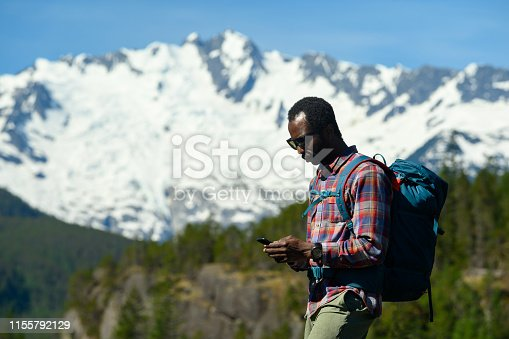 Side view of tourist using mobile phone in forest. Hiker is exploring nature against mountains. He is carrying backpack.