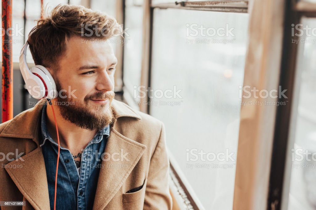 Male tourist with headphone set traveling by the bus stock photo