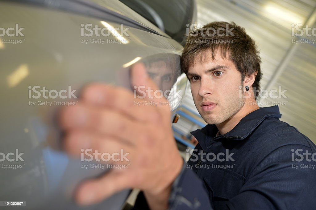 Male trainee with automobile in garage stock photo