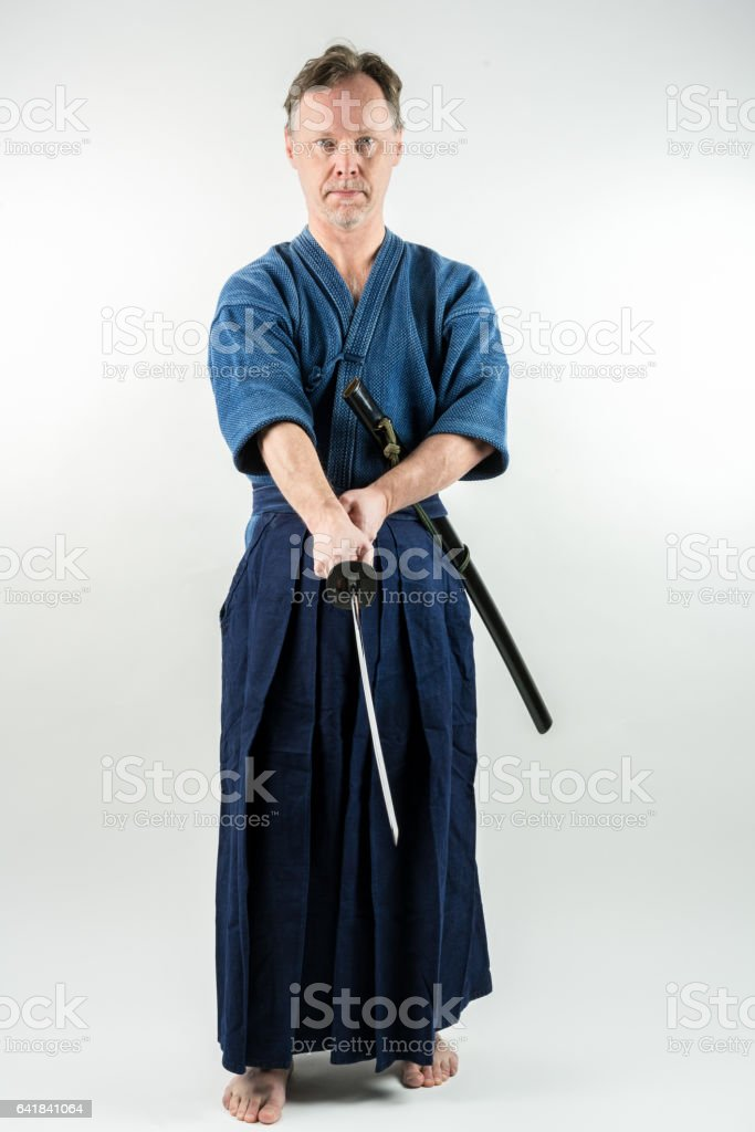 Male training Iaido holding a Japanese sword with focused look. stock photo