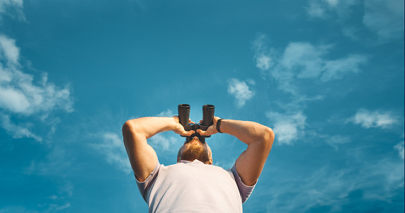 Male Traveler Looking Through Binoculars In The Distance Against The Sky. Low Angle Point Shoot