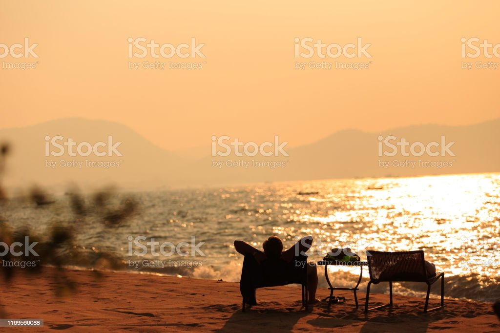 Male traveler sitting on a chair at the beach in sunset time, back...