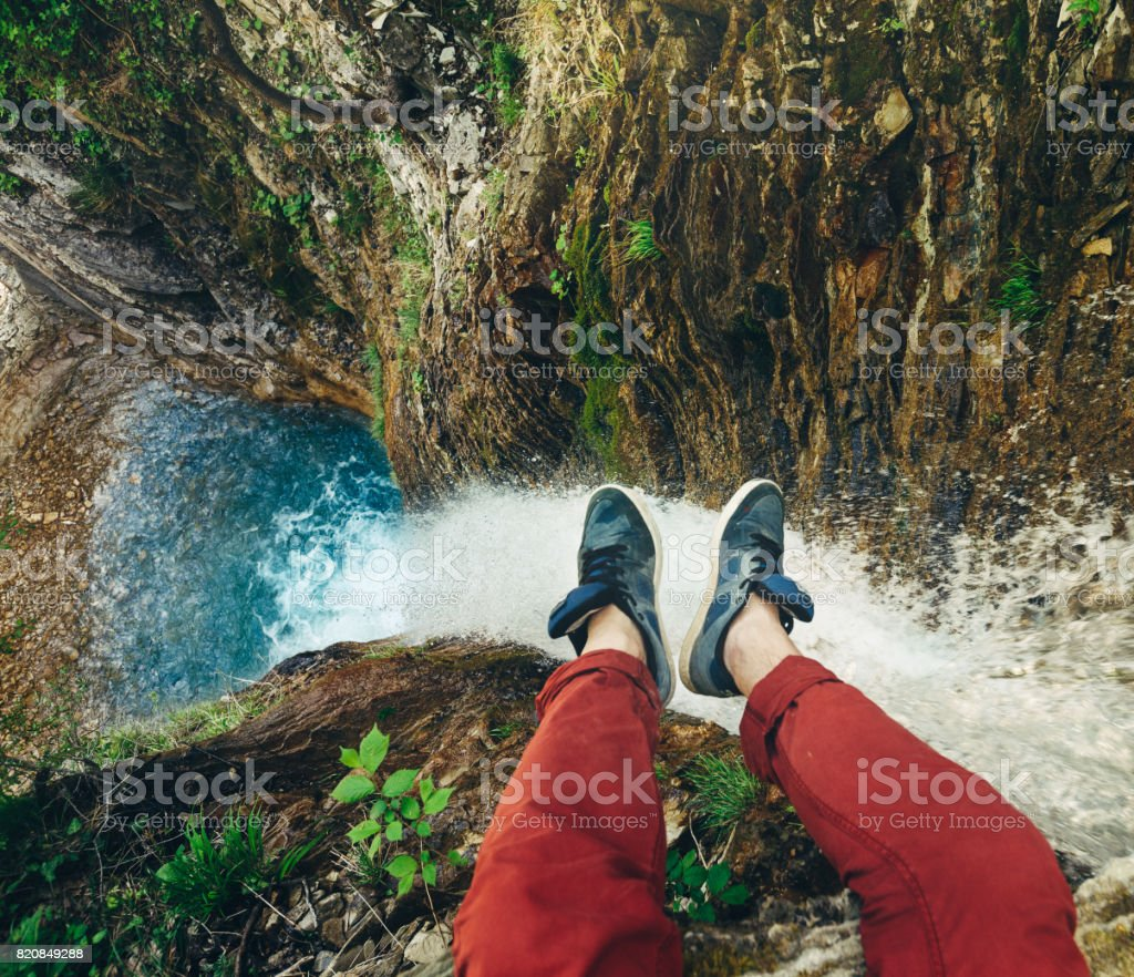 Male Traveler sitting on cliff with waterfall view. Travel Lifestyle adventure vacations concept stock photo
