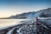 Male traveler visiting Kleifarvatn lake in Iceland with amazing snow covered mountain scenery during winter at sunset