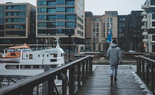 Male traveler walking on the wooden bridge near Elbe river