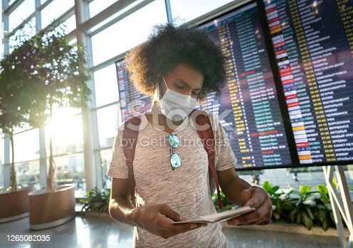 Portrait of a black male traveler wearing a facemask at the airport with the flight schedule at the background while looking at his boarding pass - travel concepts
