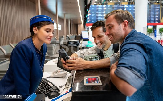 Male travelers doing the check-in at the airport using a cell phone at the counter and asking for help to the airline attendant - travel concepts