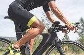 Male Caucasian cyclist races during the bicycling stage of a triathlon. He is on a highway out in a rural area surrounded by grass and pine trees, The profile shot is tightly framed and is from his feet on the pedals up to just beneath his shoulders.