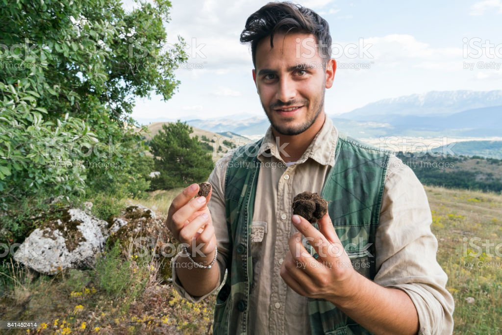 Male truffle hunter in his  20's holds a large and small truffle in his hands that he collected in the forest with his two dogs on a summer day, Abruzzo, Italy, Europe stock photo