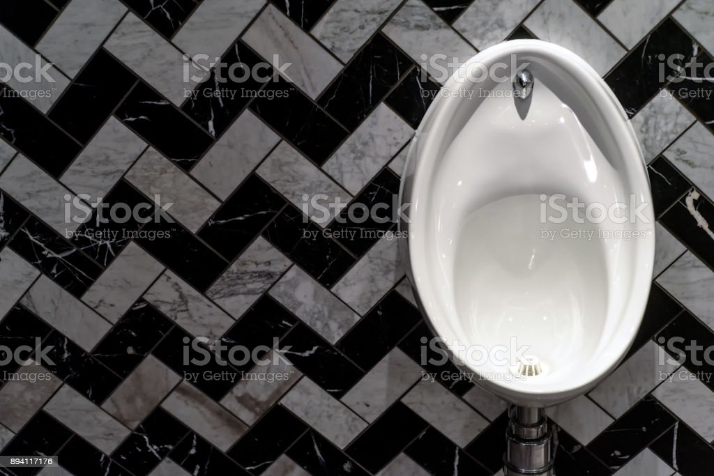 Male Urinal in White Porcelain Herringbone Tiles stock photo