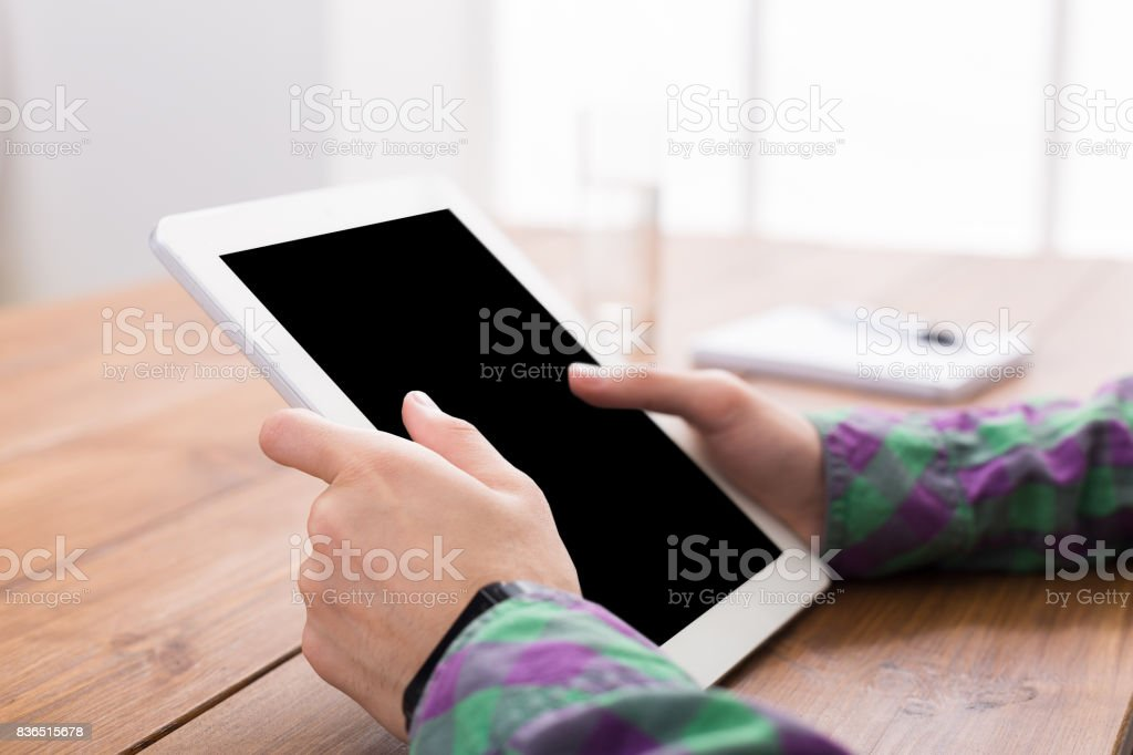 Male using digital tablet, close up, side view, stock photo