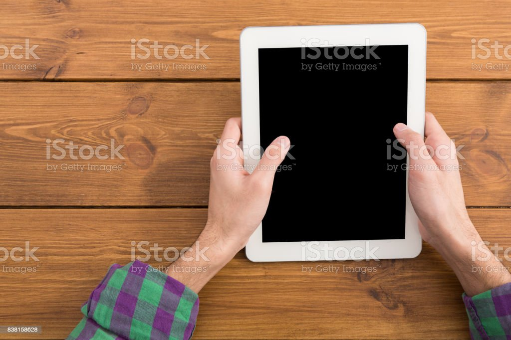 Male using digital tablet, close up, top view stock photo