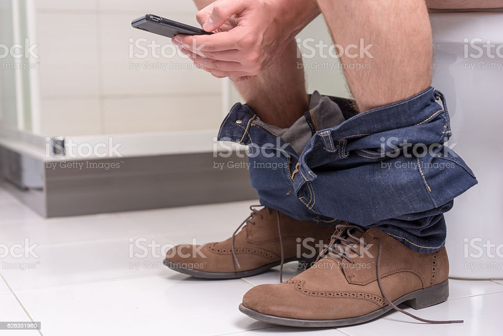 Male using phone while sitting on a toilet bowl stock photo