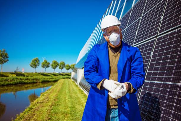 Ein männlicher Gemüsebauer an einer Solaranlage während des Ausbruchs des Coronavirus – Foto