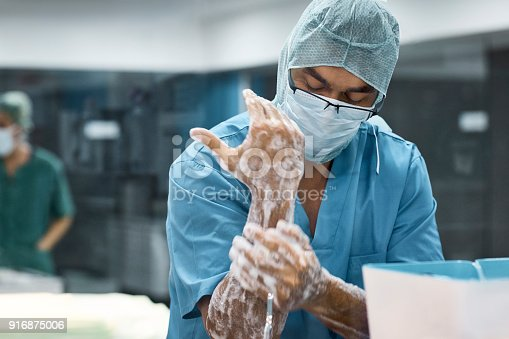 Veterinarian washing hands with soap. Male surgeon is preparing for surgery. He is in uniform at operating room.